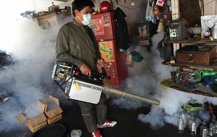 """Un employé municipal fumige une maison pour lutter contre le moustique Aedes Aegypti, vecteur du virus Zika et celui de la dengue, le 5 février 2016 à Bangkok Zika: l'OMS juge """"approprié"""" de reporter les dons de sang des voyageurs revenant des pays"""