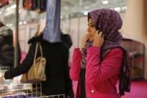 Une jeune femme essaie un foulard le 3 avril 2015, dans les allées de la rencontre annuelle des musulmans de France au Bourget Le shopping musulman a son temple au Bourget, le temps d'un week-end