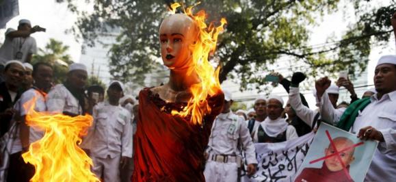 Des membres du Front des défenseurs de l'islam brûlent une effigie du moine bouddhiste Ashin Wirathu, du mouvement extrémiste 969, connu pour ses violences contre les musulmans, pendant une manifestation devant l'ambassade de Birmanie, à Jakarta (Indonésie)