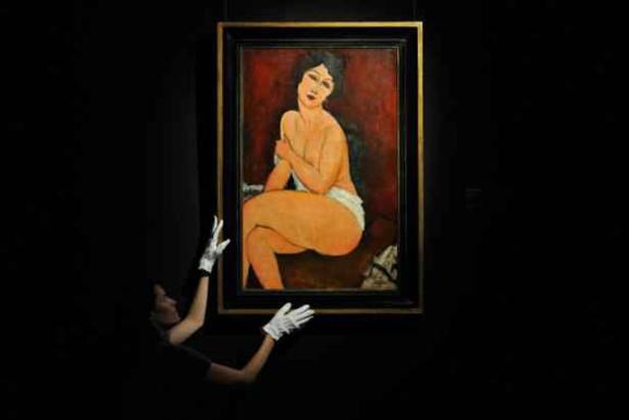"""Une employée tient une peinture de 1917, intitulée """"la belle Romaine"""", de Modigliani, chez Sotheby's à Londres le 11 octobre 2010"""